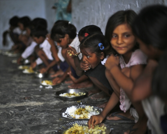 School children eat their free mid-day meal, distributed by a government-run primary school, at Brahimpur village in Chapra district, Bihar