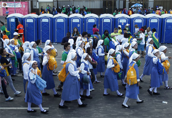 Nuns walk past port-a-potties after Pope Francis celebrated his final mass on Copacabana Beach.