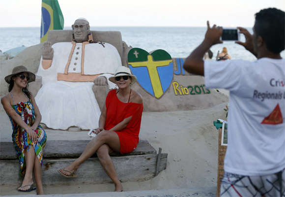Artist Rogean Rodrigues takes pictures for tourists in front of his Pope Francis sand sculpture.