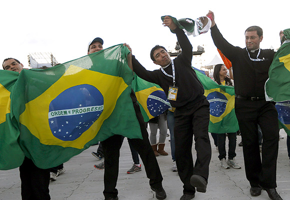 Priests dance with Brazilian flags before Pope Francis celebrates a mass at Copacabana Beach.
