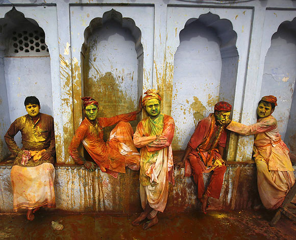 Hindu devotees covered in coloured water and powder sit in a temple during Lathmar Holi at the village of Nandgaon in Uttar Pradesh
