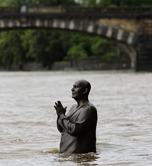 The statue of world harmony leader Sri Chinmoy is partially submerged in water from the rising Vltava river in Prague, Czech Republic.