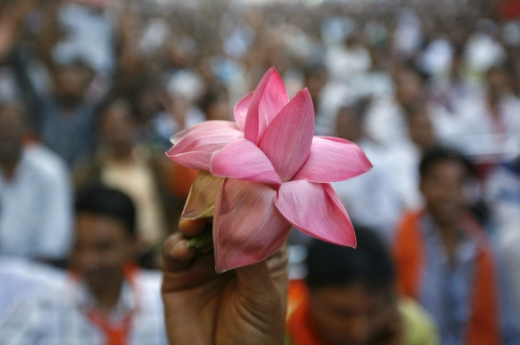 A BJP supporter holds his party's lotus symbol during a ceremony