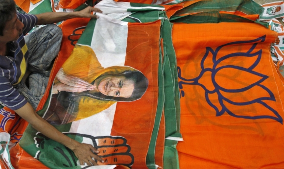 A worker looks at a Congress party flag carrying a picture of its party chief Sonia Gandhi next to flags of BJP