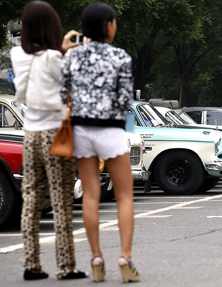 Women look around classic cars participating in the Peking-to-Paris Motor Challenge in Beijing