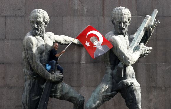 A demonstrator waves Turkey's national flag as he sits on a monument during a protest against Turkey's Prime Minister Tayyip Erdogan and his ruling AK Party in central Ankara