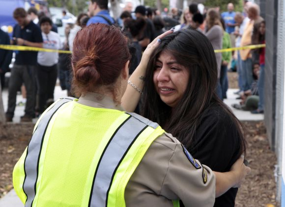 A women is comforted by a traffic officer near Santa Monica College following a shooting