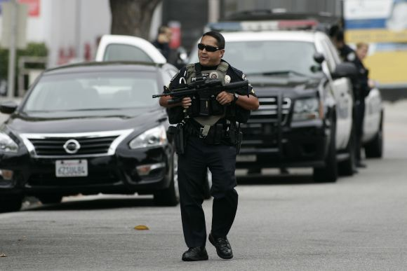 A police officer walks on the street during a search at Santa Monica College following the shooting