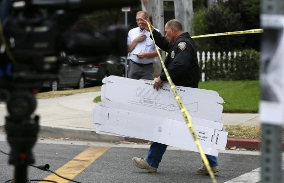 A police officer carries boxes for collecting evidence near a home which was set on fire in Santa Monica
