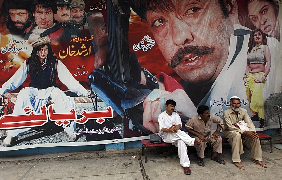 Cinema workers sit near a poster of a Pashto movie at Arshad cinema in Peshawar