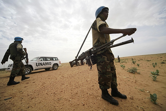 United Nations Hybrid Operation in Darfur peacekeepers stand guard as a delegation of ambassadors of European Union to Sudan visits a women development program centre funded by World Food Programme at Shagra village in North Darfur