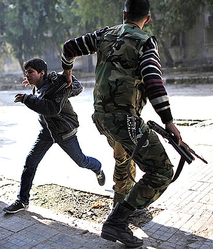A Free Syrian Army fighter pulls a boy off the street as a sniper fires during fighting with forces loyal to Syrian President Bashar el-Assad in Aleppo city