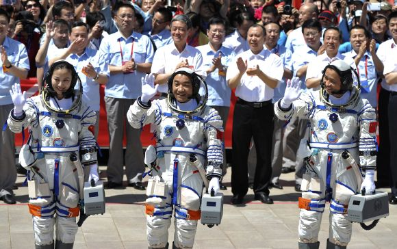 Chinese astronauts (from L to R) Wang Yaping, Zhang Xiaoguang and Nie Haisheng wave before leaving for the Shenzhou-10 mission.