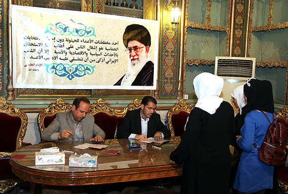 Members of the election commission work during the Iranian presidential election at al-Mhsinya school in Damascus examining the papers of Iranian women living in Syria who came for a vote