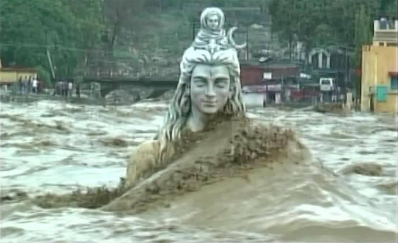 Huge waves of River Ganga crash over the statue of Lord Shiva in Rishikesh