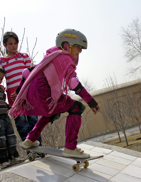 Wearing helmet and knee guards, a girl tries some new skateboarding tricks in Kabul, Afghanistan