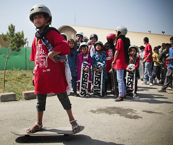 An Aghan teenage girl tries balancing on the skateboard during a session while others await their turn