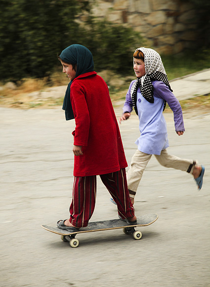 An orphan Afghan girl skateboards in Kabul as her friend tries to catch up
