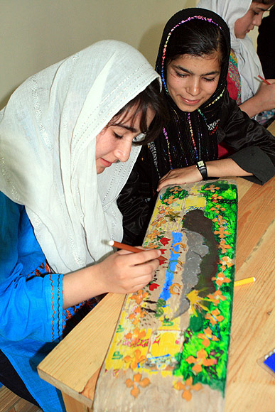 A student paints her skateboard at the centre in Kabul