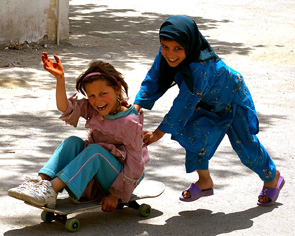 Two girls from the Kufa Orphange in Kabul play around with the skateboard