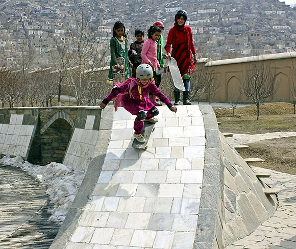 A girl slides down the skating ramp in a garden in Kabul as her friends watch in awe