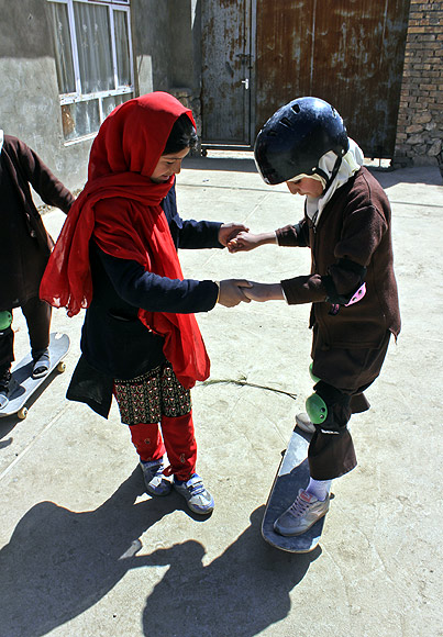 An Afghan girl helps her friend to learn skating in Kabul