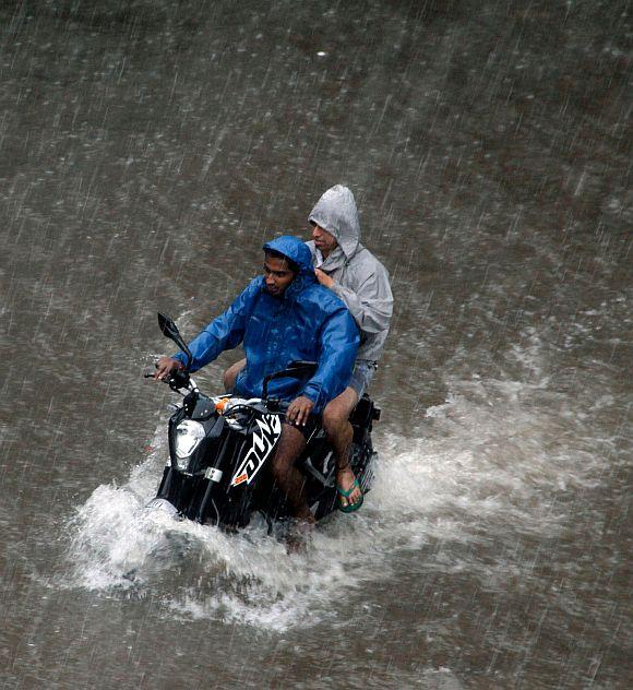 Motorists wade through a flooded street in Dadar