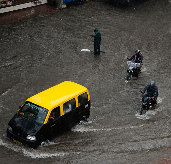 A taxi plies on a flooded street at Sion