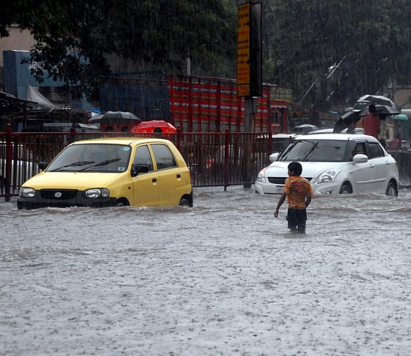 A boy tries to cross a flooded road in Parel