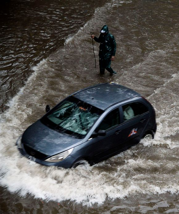 A car makes its way through a flooded street in Andheri