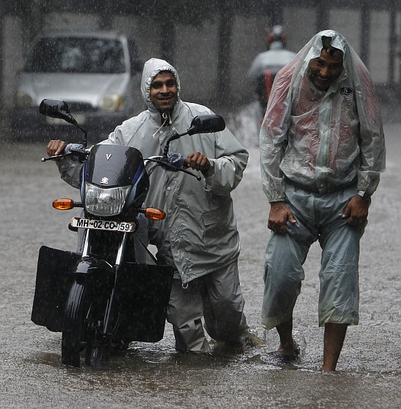 A man pushes his stalled motorcycle through a flooded street as his friend walks with him during monsoon rains in Mumbai