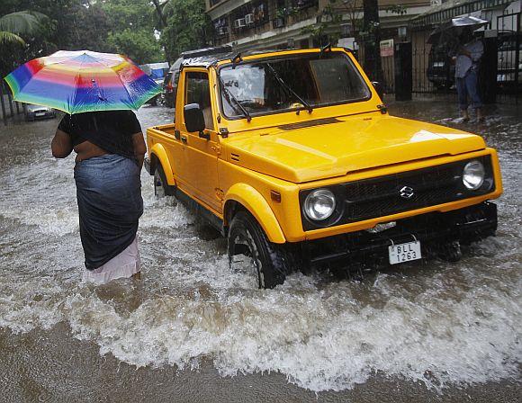 A woman walks through a flooded street as as a four-wheel drive vehicle passes her during monsoon rains in Mumbai