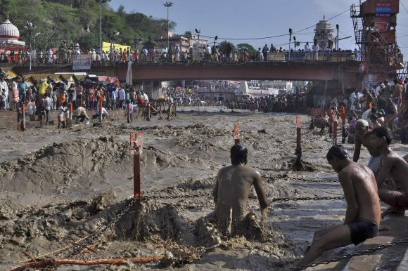 A Hindu devotee tries to take a holy dip in the flooded waters of river Ganges in the northern Indian town of Haridwar