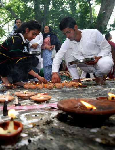 Kashmiri Pandit families light diyas while they offer prayers at Khir Bhawani temple in Tullamulla on Monday