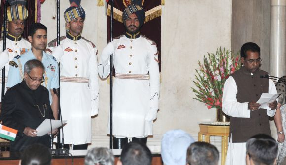 President Pranab Mukherjee administering the oath as Minister of State to Jesudasu Seelam in Rashtrapati Bhavan on Monday.