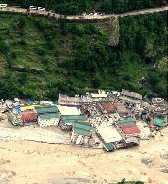 This image shows a flash flood near a settlement in Uttarakhand