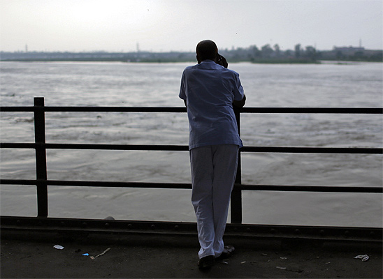 A man stands under a bridge built over river Yamuna in New Delhi