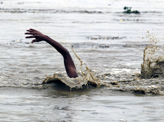 A man swims in the flooded waters of river Yamuna