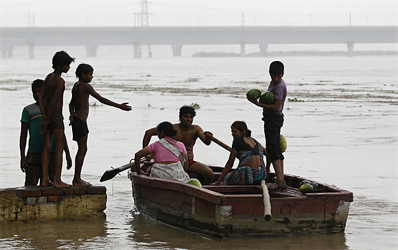 A man ferries his boat after retrieving floating watermelons from the flooded waters of river Yamuna in New Delhi