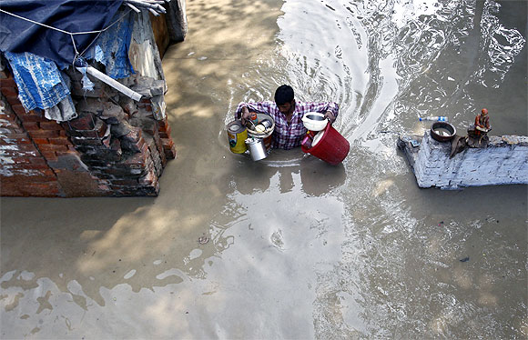A resident carries his belongings through an alley flooded with the rising water level of river Yamuna after heavy monsoon rains in New Delhi