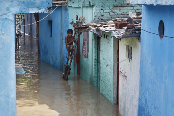 A boy sits on a ladder next to his flooded house with the rising water level of river Yamuna after heavy monsoon rains in New Delhi