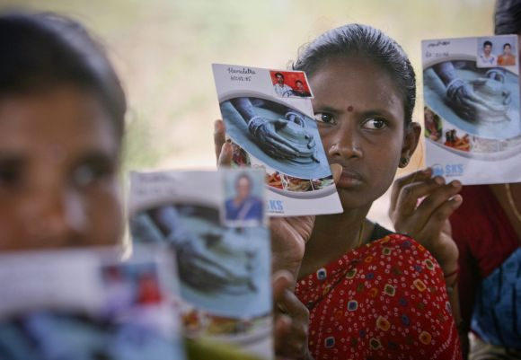 Rural loan borrowers show pass books given to them by a micro finance company at a village in Andhra Pradesh
