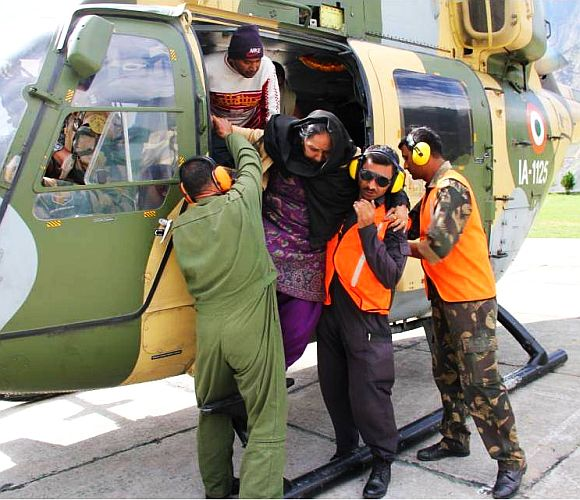 An army helicopter rescues stranded people in rain ravaged Uttarakhand on Thursday