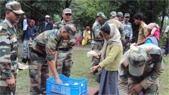 Rescued people being provided food packets in rain-devastated Uttarakhand on Thursday
