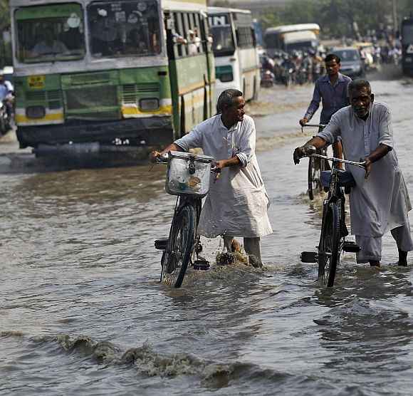 Commuters push their bicycles through a flooded road after heavy monsoon rains caused the rise in waters of Yamuna river in New Delhi