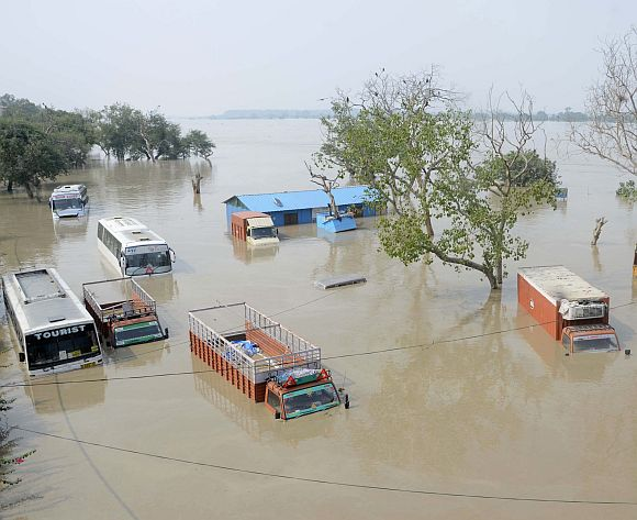 Vehicles are submerged in the rising waters of the river