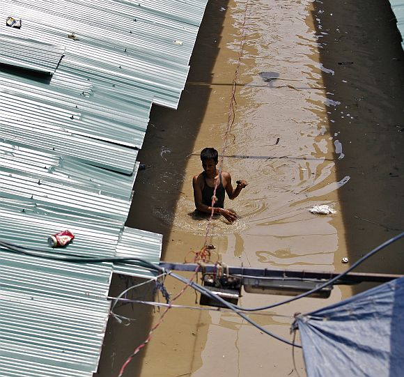 A man wades through a flooded alley at a shopping arcade after heavy monsoon rains caused the rise in waters of Yamuna