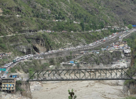 Stranded vehicles stand in queues after heavy rains in the Himalayan state