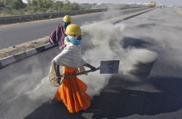A woman labourer spreads black ash over a newly constructed road at Raipur village, in Gujarat