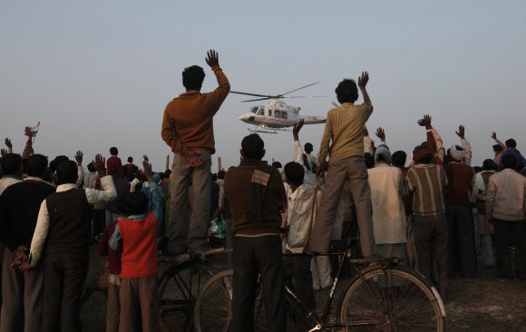 Villagers wave towards a political leader's helicopter